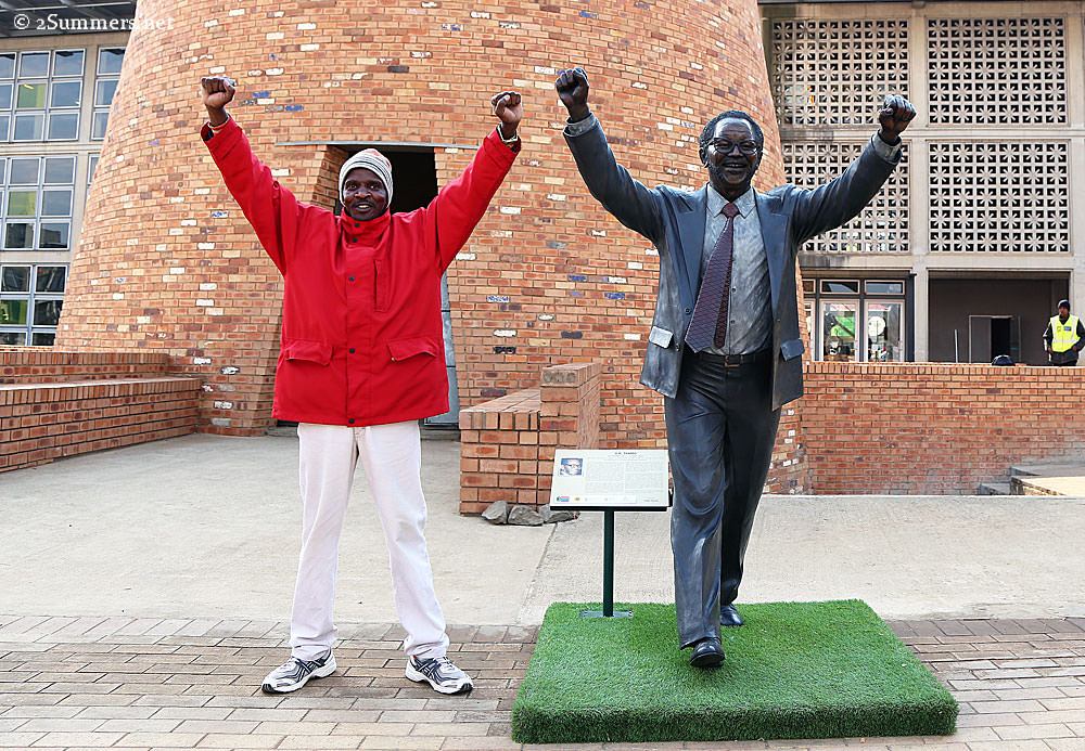 Man posing with statue of Walter Sisulu