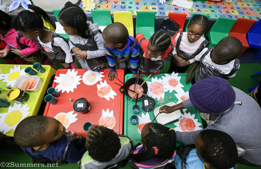 Birds-eye view of kids painting at Grow Up and Learn School
