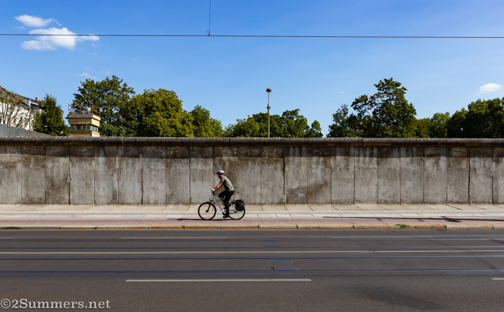 Cyclist passing the Berlin Wall