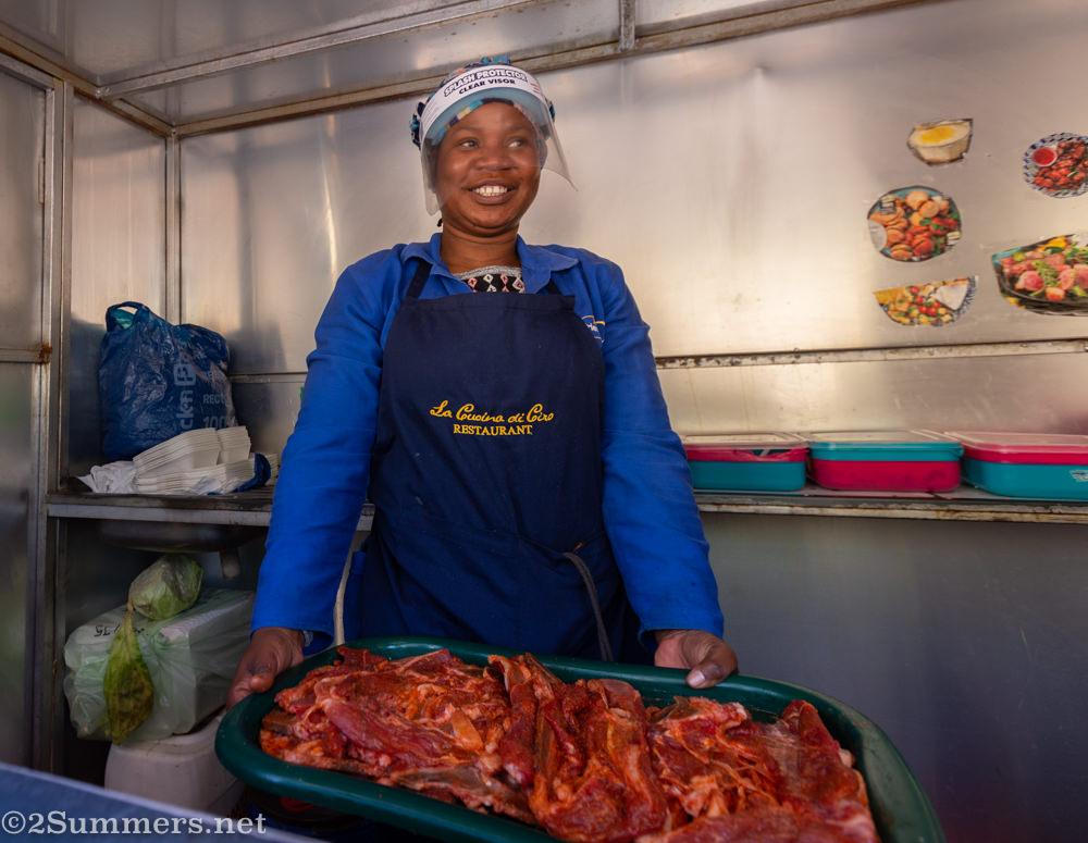 Mbali preparing meat in her food trailer