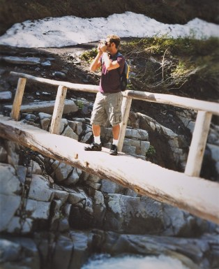 Chris Taylor crossing Log Bridge over Nisqually River in Mt Rainier National Park 2traveldads.com