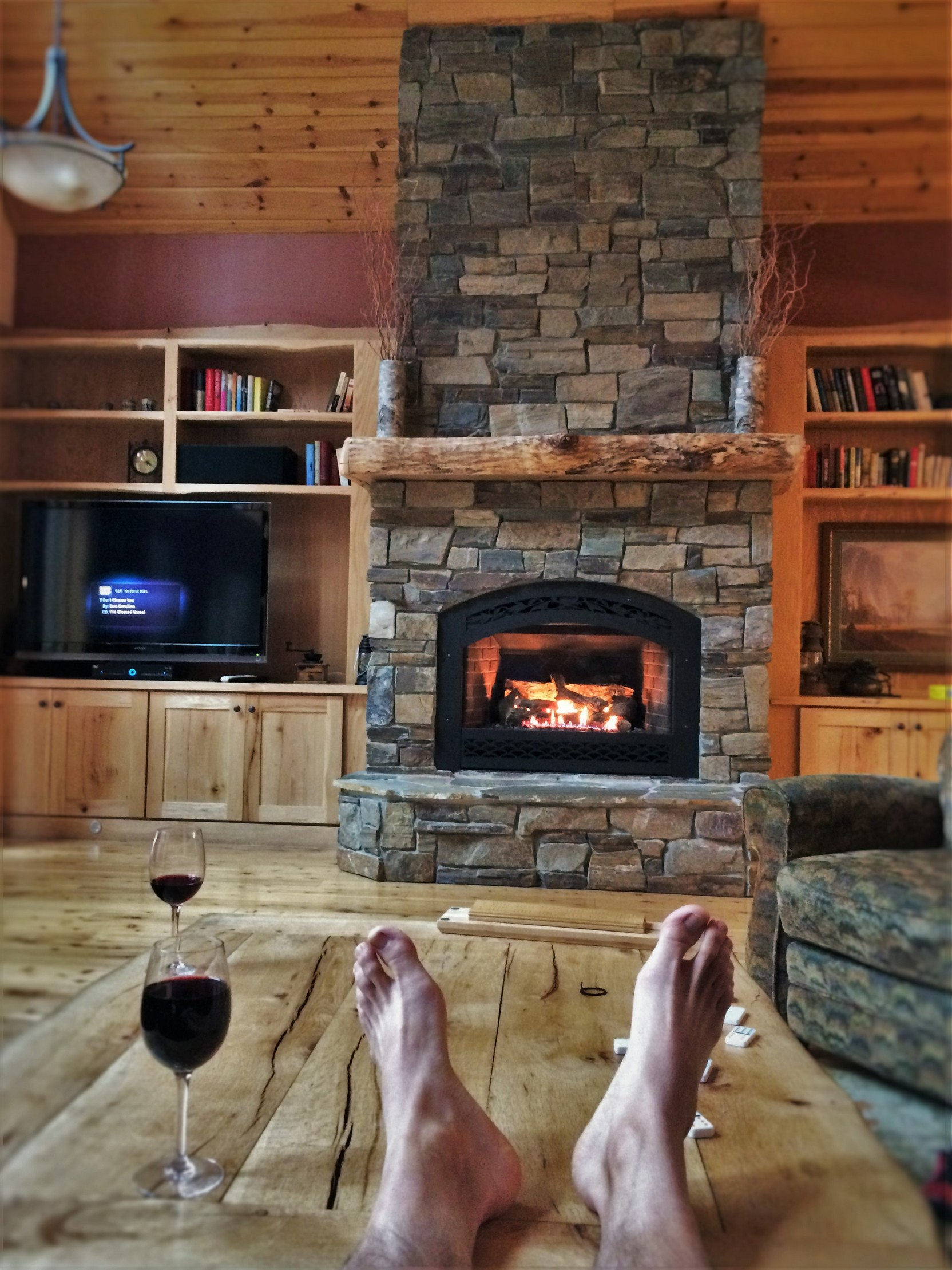rob taylor feet and wine with stone fireplace in john muir house
