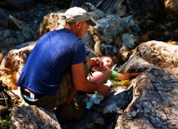 Rob Taylor and TinyMan diaper change on rocks at Silver Falls Mt Rainier National Park 1