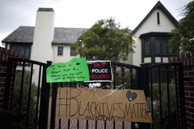 Signs protesting the death of Ezell Ford, who was shot by police, are left by protesters outside the home of Los Angeles mayor Eric Garcetti in Los Angeles, California June 9, 2015. The Los Angeles police commission on Tuesday will review the findings of the city's police chief and an inspector general that two officers were justified in opening fire on an unarmed black man who investigators say tried to grab one officer's gun. REUTERS/Lucy Nicholson - RTX1FUUS