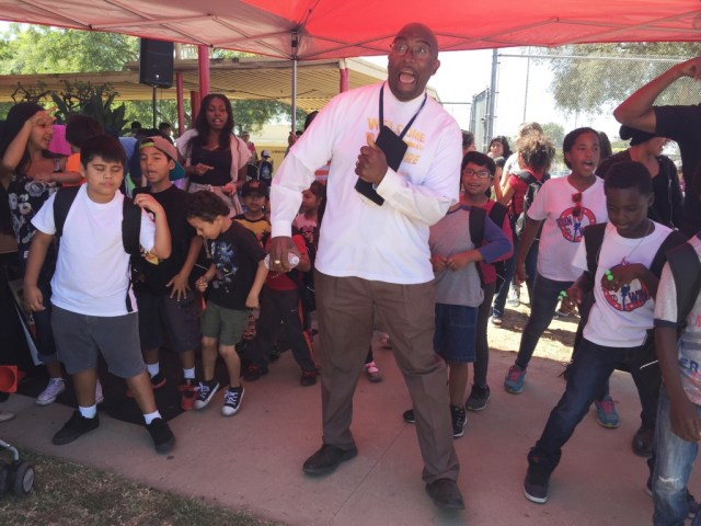 """State-appointed administrator Vincent Matthews dances the """"Cupid Shuffle"""" with students at a back-to-school event August 19, 2016. PRISKA NEELY/KPCC"""