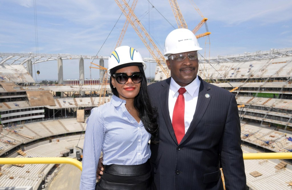 Inglewood Mayor James Butts Jr. and Melanie McDade-Dickens pose at the NFL stadium during construction in April. The site will be the home of the Los Angeles Chargers and the Los Angeles Rams plus Super Bowl LVI in 2022 and the College Football National Championship in 2023 and the opening and closing ceremonies of the 2028 Olympic Games. (Photo by Kirby Lee, USA TODAY Sports via Reuters)