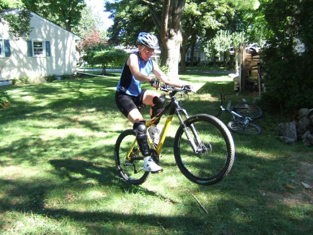 Terri with good backyard wheelie form, arms extended and torsovertical
