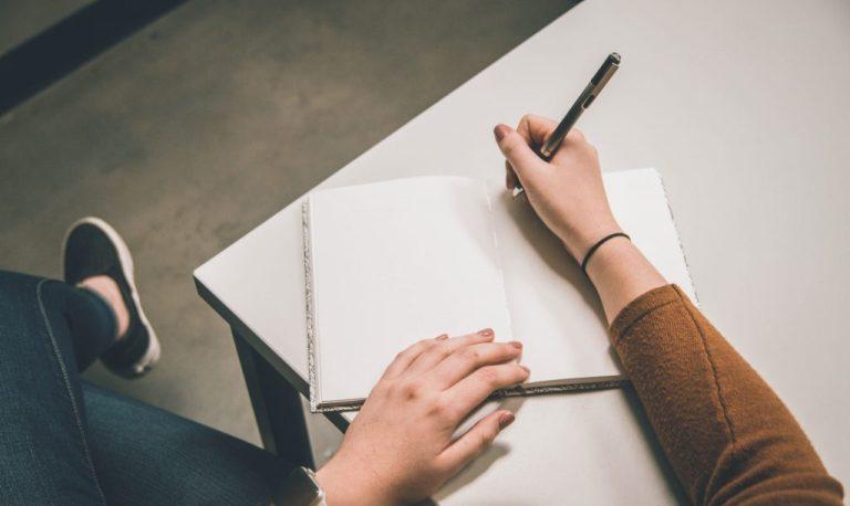 femme positive qui écrit ses objectifs sur un bout de papier