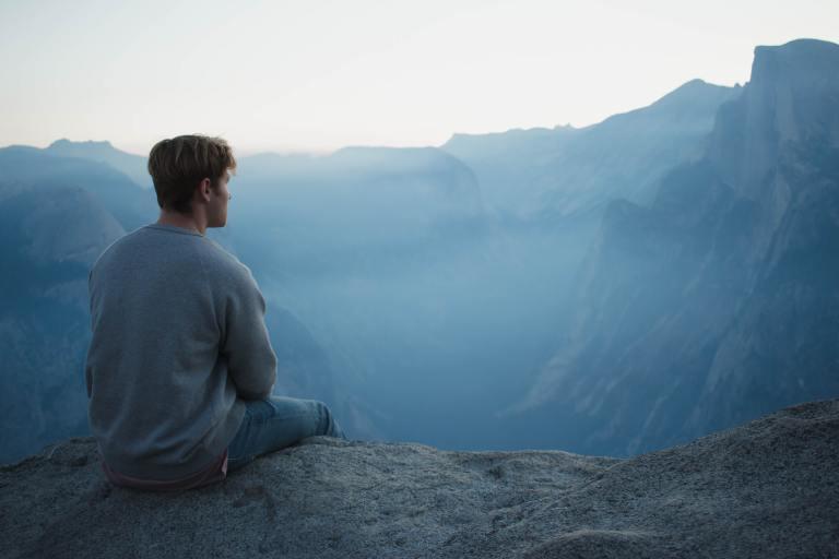 homme qui regarde les montagnes en cherchant à comprendre comment s'améliorer