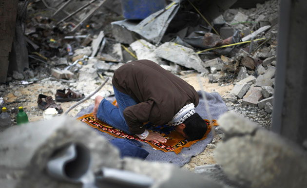 Palestinian citizen doing his prayer over his house which  was demolished by the Israeli air raids and ground incursions in the last Israeli war in Gaza.