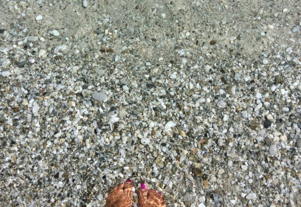standing in the crystal clear water at Plage Argent