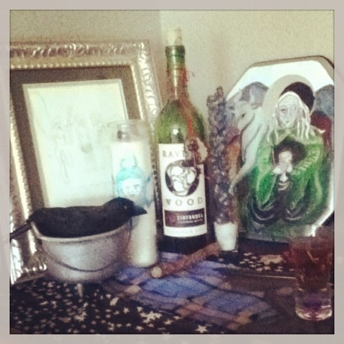How to set up an altar. If you are like me, and are a witch that works with gods or other powers, you might want to have an altar or two in you living space. This is a space you will do your witchery and chill with the spirits or deities you prefer. But for some reason, altars tend to be intimidating! You see other witches' altars and its just like, OH GODS I DON'T HAVE STUFF!!! Look, you probably do have stuff, you just don't realize how nice it might look together and how meaningful it could be for you and your powers.  So let me help you out from the ground up. First colors—a pretty altar has some color coordination. Pick one piece that has a few different colors in it for your anchor to the altar. Determine what color family it is in. Spring, Summer, Fall, or Winter Colors?  What is this starting piece? It might be a work of art. I have used framed greeting cards, post cards, and small print offs from my computer for my altars—and I have painted, collaged and drawn my own, most anything looks good framed. You can use a frame you already have, buy one at a discount store, or make one out of stuff you have like construction paper or wrapping paper. Another good piece that might have a few colors is a scarf that you can use as an altar cloth. Once you have a color scheme, pick out other things that look good color and pattern wise with your main piece. You might have another scarf that is a complimenting or matching shade or even some lace that you can layer with your other altar cloth.  Often some sort of dishes end up on an altar, a plate, bowl or cup of some kind for offerings. If you have one or more of these, make sure they look good together. You can go for a matching set, or go for the funky mismatched look, as long as the colors and patterns seem to work out together. I used a glass shot glass and a small cheap cauldron and crow decoration from Halloween. Many altars have candles and along with that candle holders. You can go as simple as a little tea light on a dish, or a jar or seven day candle. If you get a colored candle, try to get one in the same color family as the rest of your altar. If you end up with a candle holder, look for designs that go well with your other components. A really gorgeous lantern or lamp could be your focal point for the whole altar and draw everything together, it might even be something you already had in your family. I used a shot glass with rock salt in it to hold my candle. You can also use wine bottles to hold candles. The key here is never discount things you already have! In a nice arrangement with color family taken into account you can have a gorgeous altar in no time.
