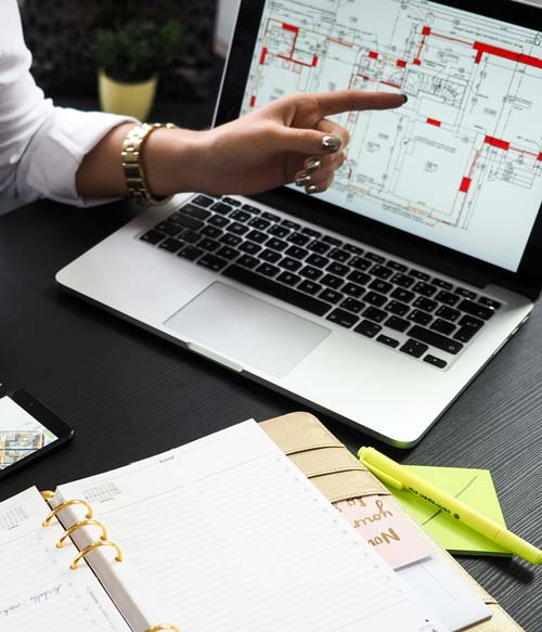 woman pointing at a blueprint on a laptop