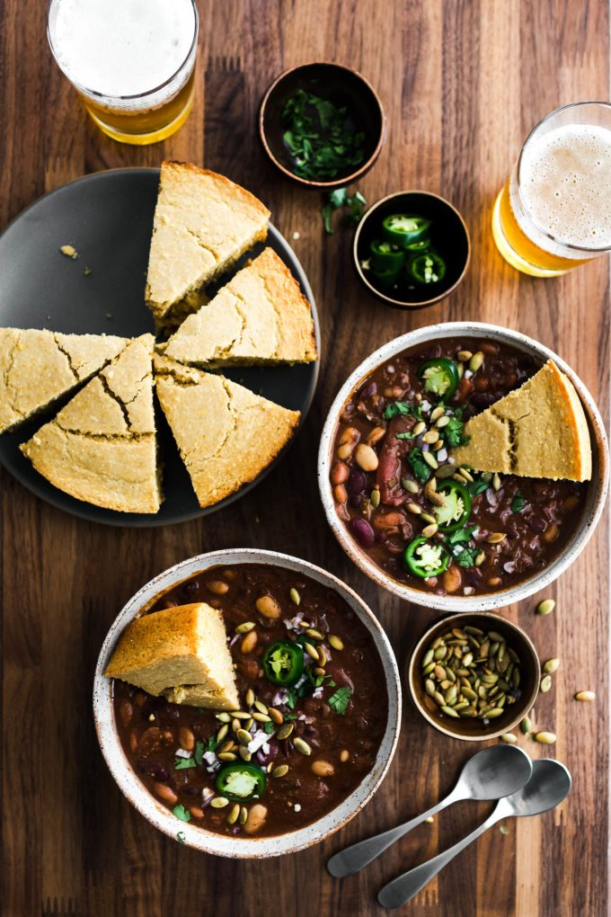 Overhead shot of two bowls of vegan chili filled with beans and topped with jalapeños and cornbread.