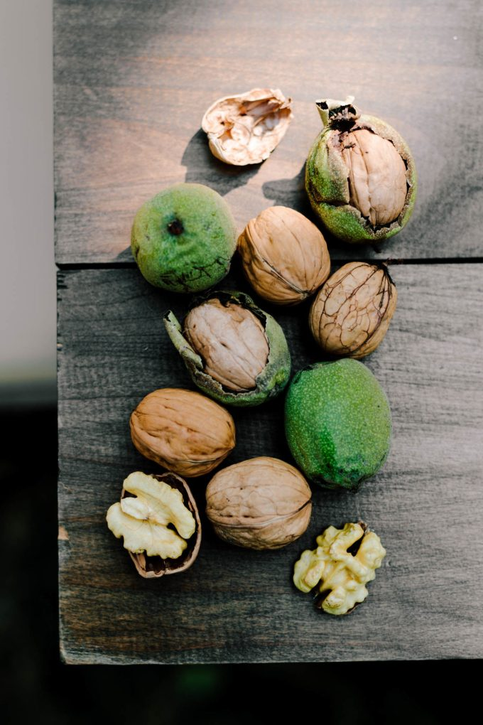 overhead shot of walnuts in different stages including in the hull and cracked.