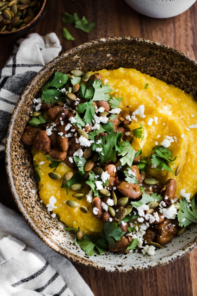 Close-up overhead photo of pumpkin polenta topped with chipotle pinto beans and cilantro