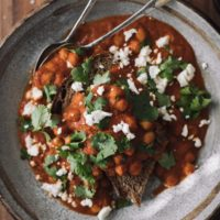 Overhead shot of chickpeas in a rich tomato sauce, all on a piece of toast.