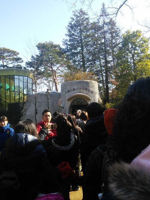 A group of people waiting in line outside the entrance to the Studio Ghibli Museum