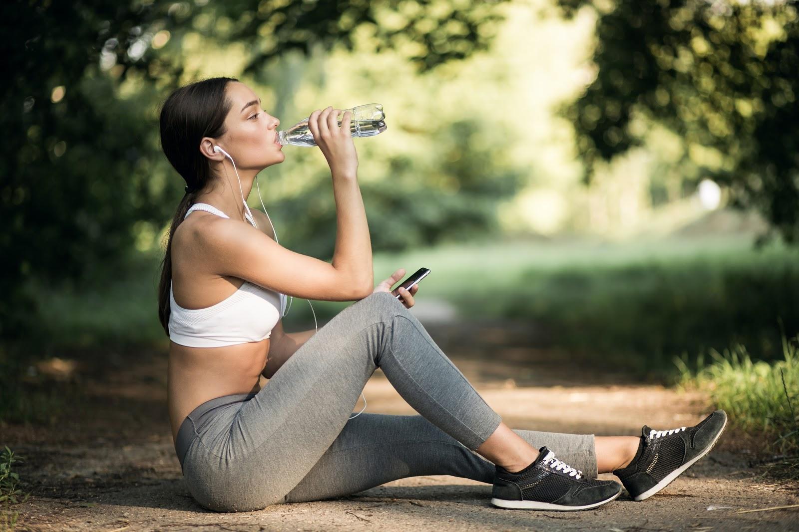 mulher sentada no chao de um parque com roupas esportivas tomando agua