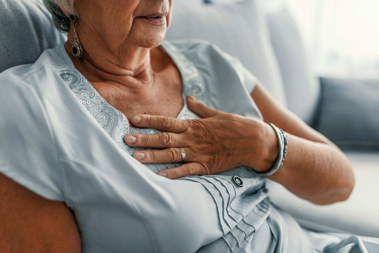 senhora com a mão no peito demonstrando dor