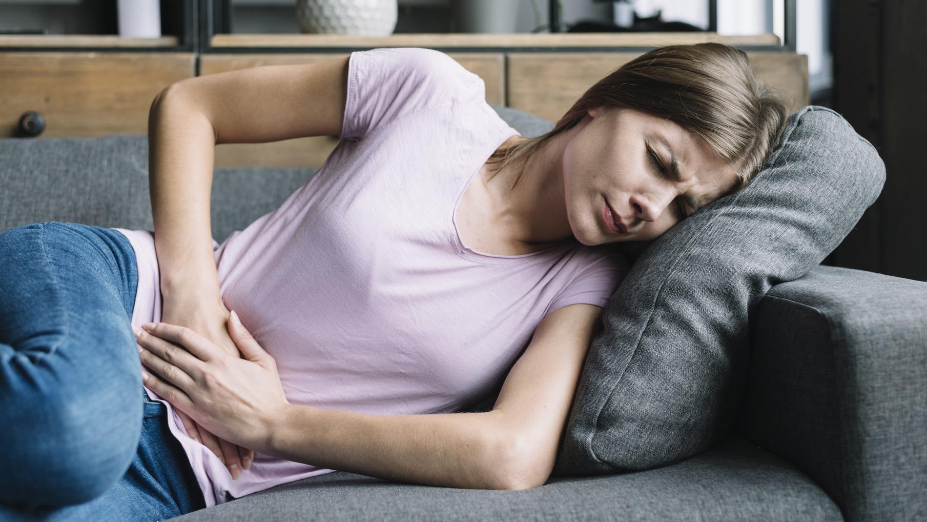 mulher deitada com as maos na barriga aparentando dor