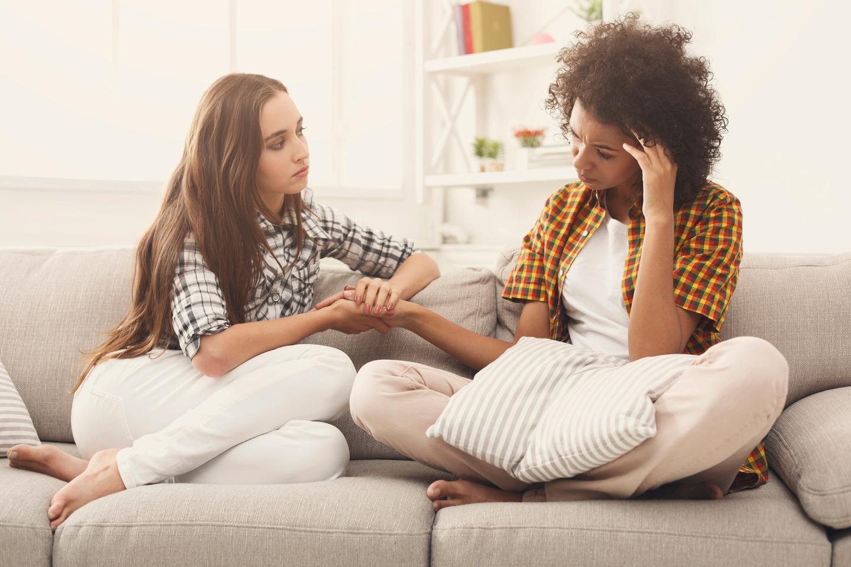 duas mulheres conversando sentadas no sofa