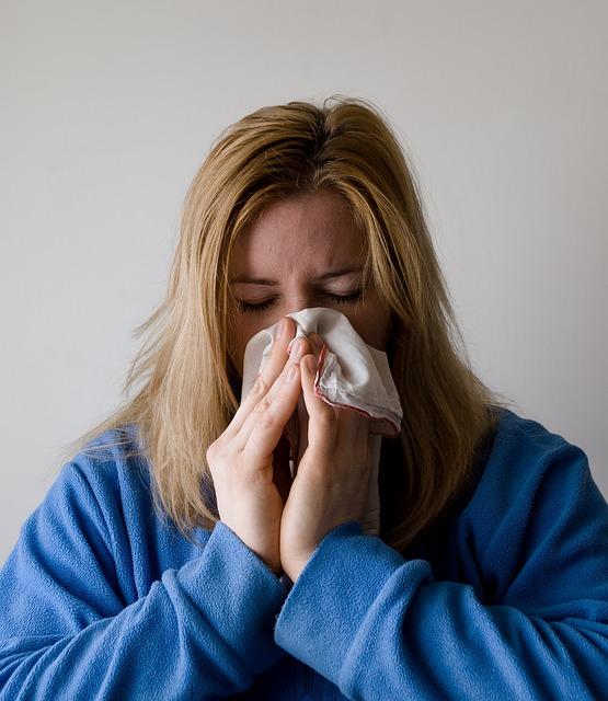 mulher com as maos assoando o nariz usando um papel higienico