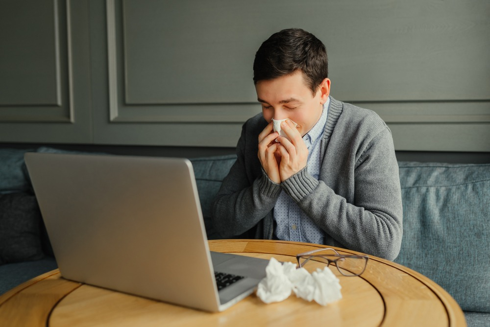 homem com as maos assoando o nariz usando um papel higienico