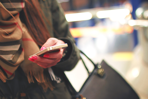 woman with a phone in her hand, perhaps using facebook messenger for business