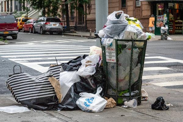 NYC litter basket overflowing with plastic bags