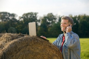 Guy on the phone on a haybale