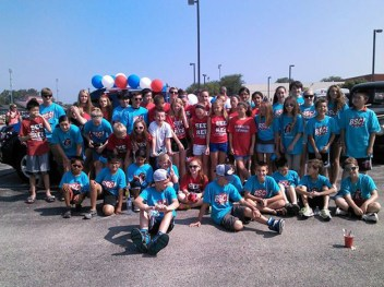 Barrington Swim Club lines up for walking in the parade outside the high school parking lot - Kim Emary