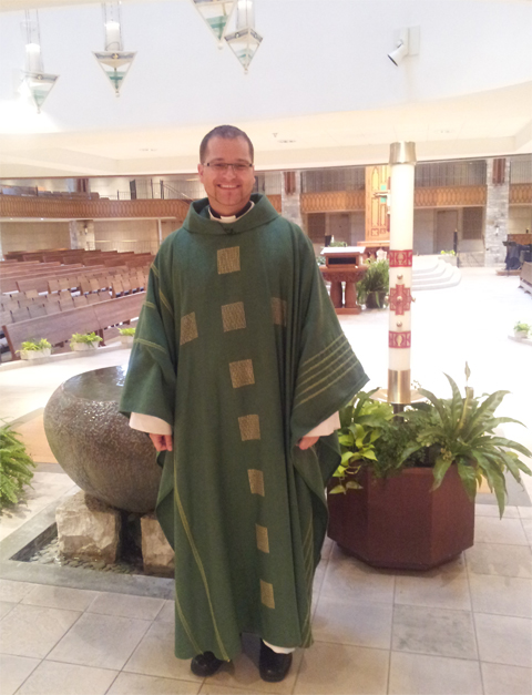 Father Chris Ciastoń, the new associate pastor of St. Anne's, stands at the baptismal font. Photo courtesy of Karen McBride.