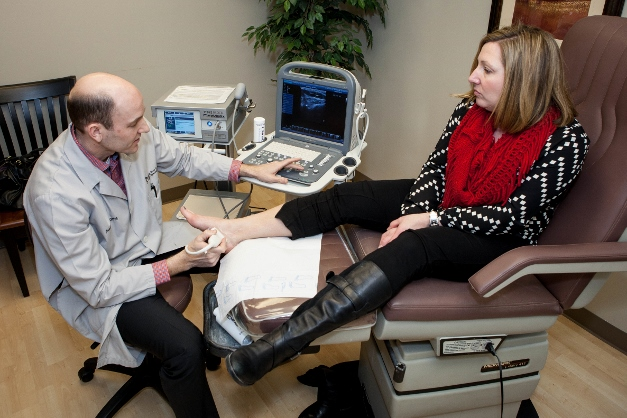 Dr. James Baird uses ultrasound to locate patient Jenn Wondrasek 's injury - Photographed by Liz Benedetto