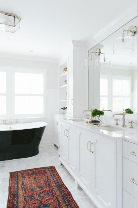All-white bathroom with dark tub & vintage runner