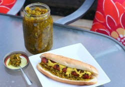 Jar of homemade cucumber relish and hot dog on a patio table