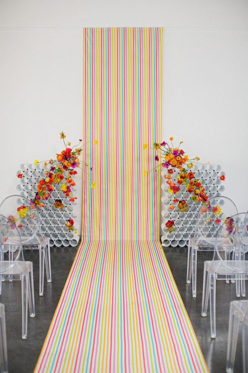 neon verticle stripe background and aisle runner with modern sculpural flowers and clear chairs