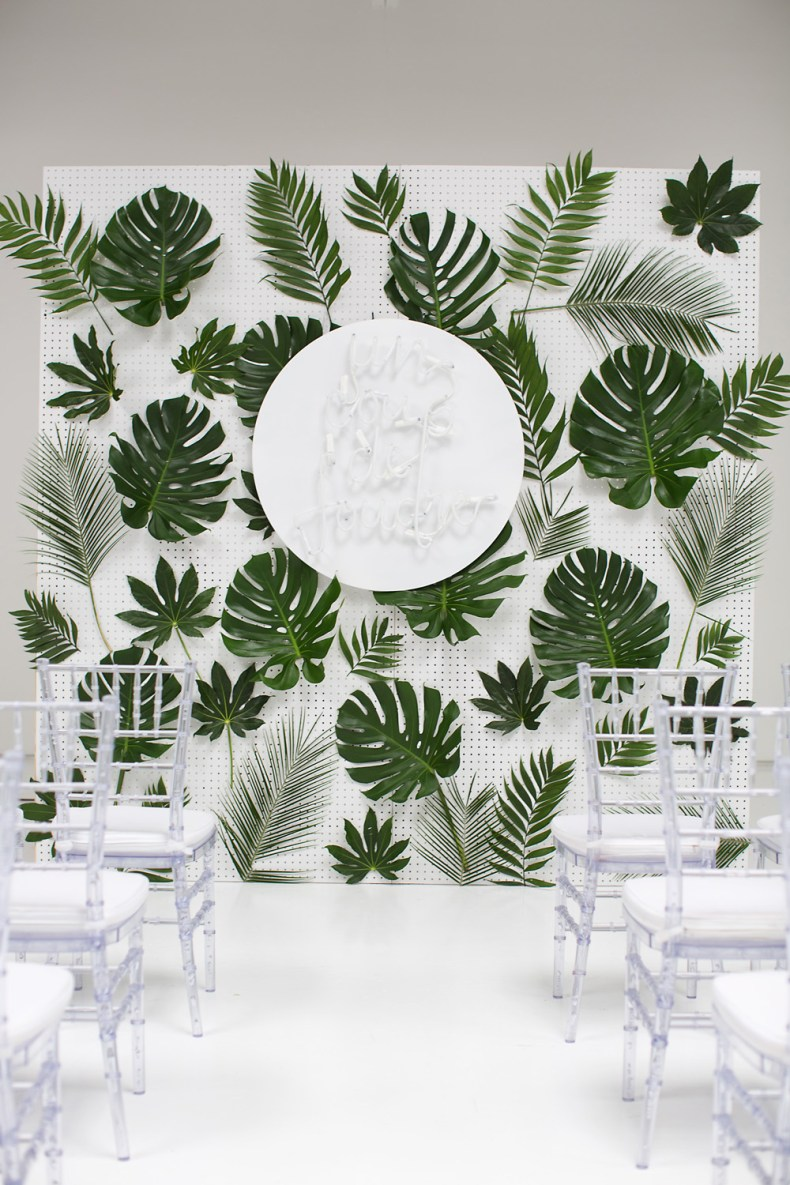 tropical leaf collage on white pegboard wall