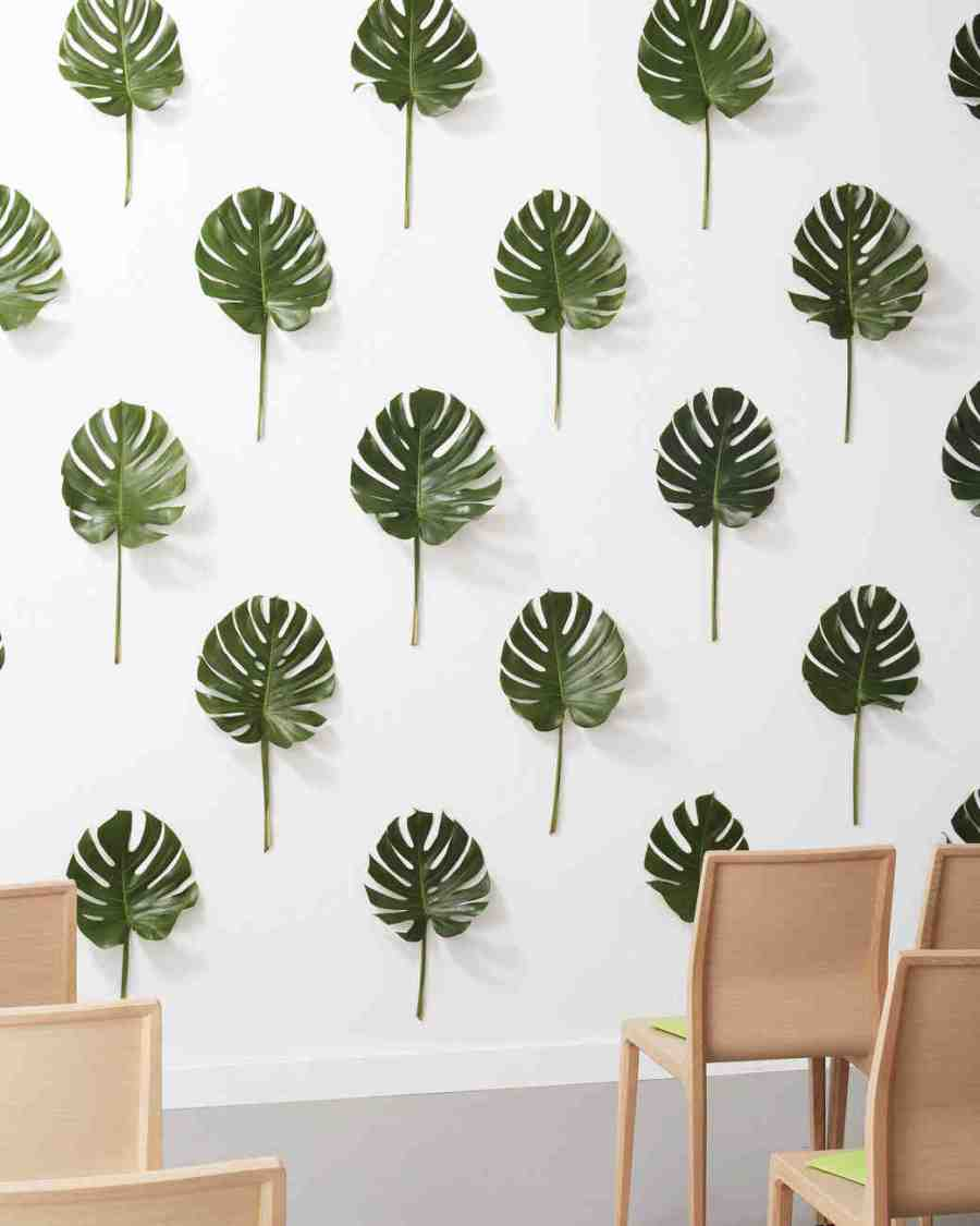 tropical leaves hung vertically on a wall and evenly spaced to create three-dimensional wallpaper-like pattern