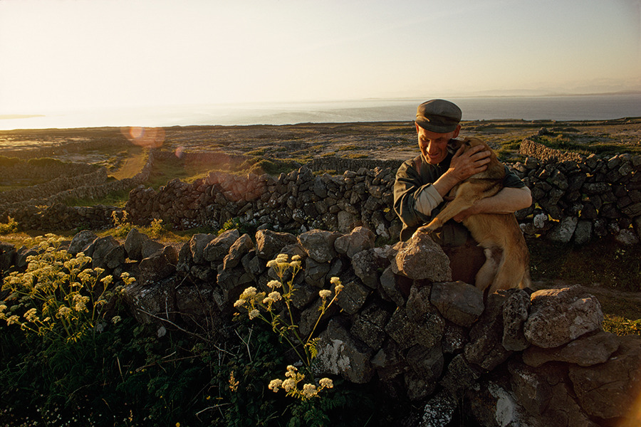 A farmer embraces his dog in his stonewalled field on Inishmore Island in Ireland, March 1971.Photograph by Winfield Parks, National Geographic Creative