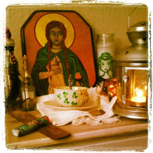 My new Brìde/ancestor shrine. Today is my vigil. I regard Brìde as my spiritual ancestress as she is the patron saintess of Ireland my ancestral homeland. I have my ancestor spirit bottles on the same shrine and will be adding my ancestor photos and family tree book when my mother finishes making those for me. Today is also my flame tending vigil. I am still adjusting to combining my various practices, but as my overall animist faery faith views integrate pretty seamlessly with my traditional witchcraft, the adjustment has been easier than one might suppose.