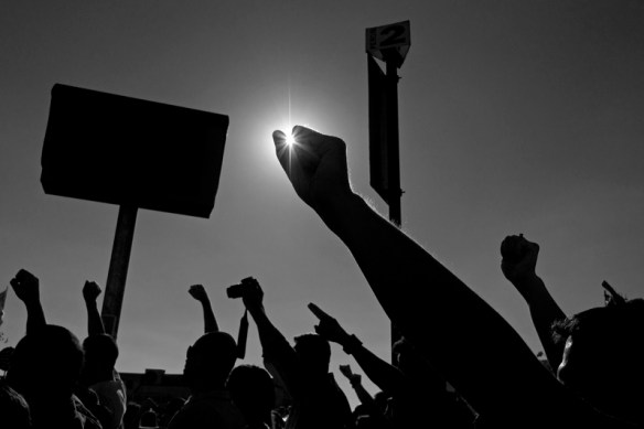 A silhouette of raised hands and placards against the sun