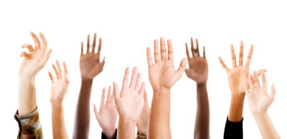 A photograph of hands raised in the air, to indicate voting