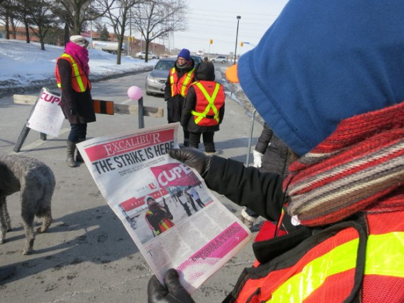 A picket captain reads a copy of The Excalibur, with news of the CUPE 3903 strike on the front page.