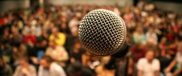 A picture of a microphone in front of a large audience