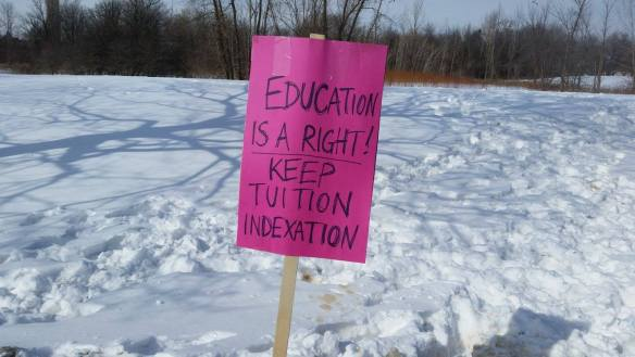 "A pink sign in the snow reads ""Education is a right! Keep tuition indexation""."