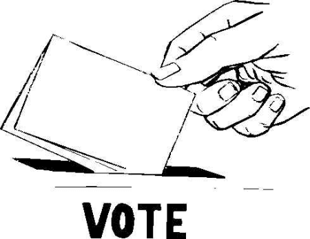 A hand places a ballot in a ballot box.
