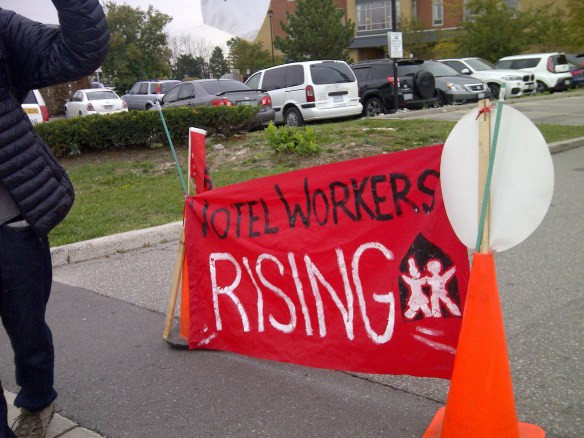 "A red banner from the UNITE HERE Local 75 picket line reads ""Hotel Workers Rising""."