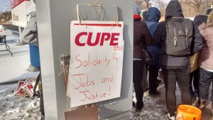 "A sign on a picket line reads ""Solidarity for Jobs and Justice""."