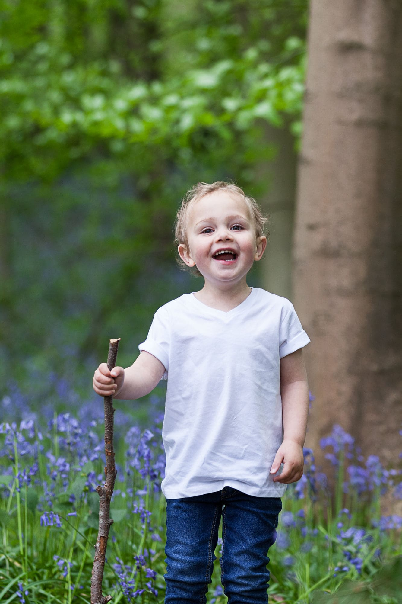little boy with a stick at his Bexley family bluebell shoot